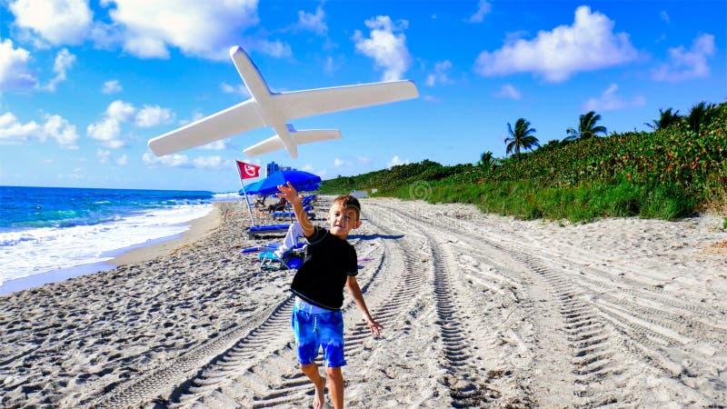 重新开放后,身穿泳装的快乐男孩在海滩上玩耍 玩飞机的孩子 免版税图库摄影