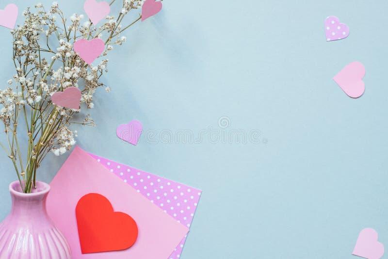 重点 与心脏的华伦泰在蓝色背景的卡片和花 复制空间 免版税图库摄影