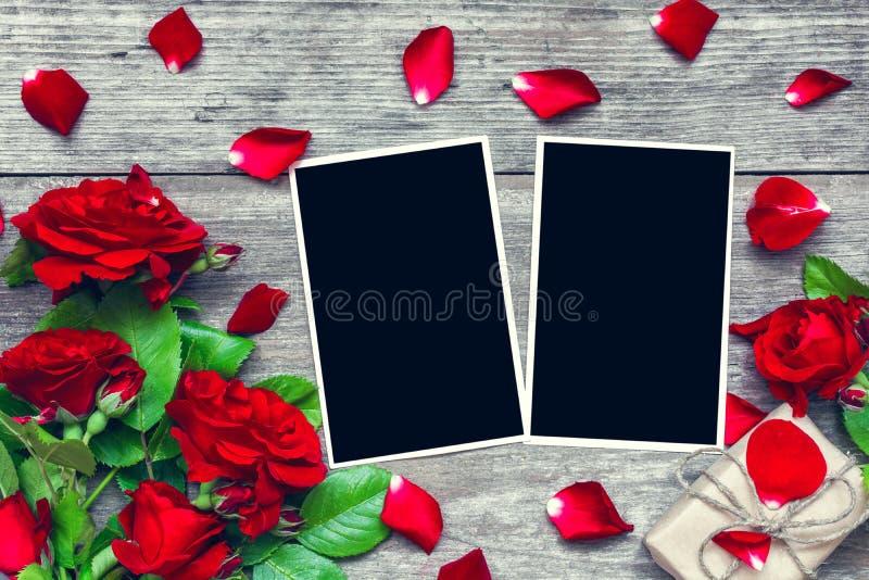 重点 与红色玫瑰的空白的照片框架开花花束和礼物盒 免版税库存照片