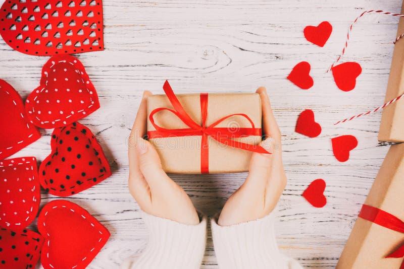 重点 女孩手给华伦泰有红心里面的在一白色定调子,葡萄酒老木桌礼物盒 免版税库存照片