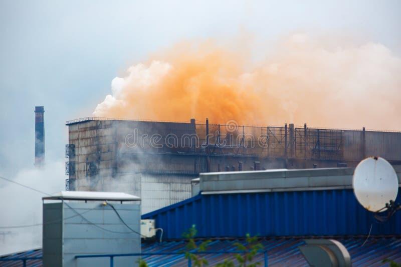重的工业铁植物放射到大气里,橙色烟云彩从老铁工厂的 库存照片