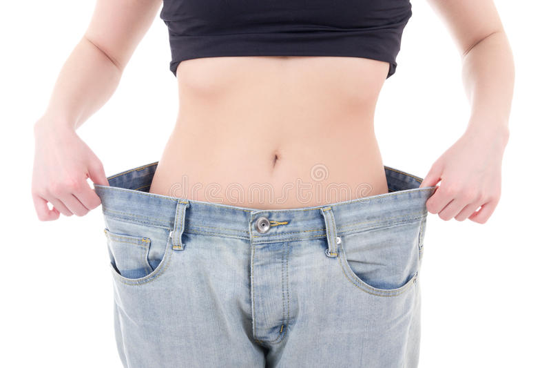 重量损失概念-在白色隔绝的大牛仔裤的亭亭玉立的妇女 库存照片