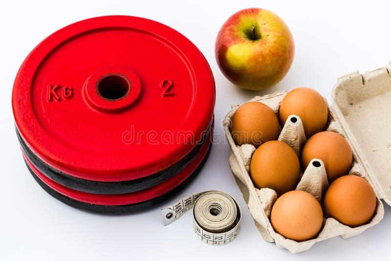 重量板材、鸡蛋、苹果计算机和测量的磁带。健身和Nutri 免版税图库摄影