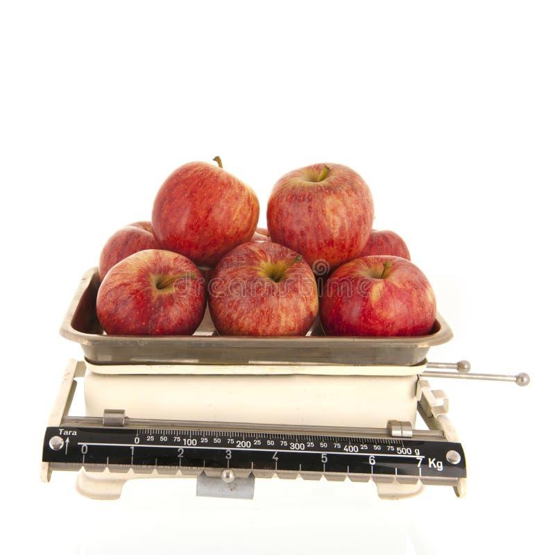 重量标度新鲜的苹果被隔绝在白色背景 库存照片