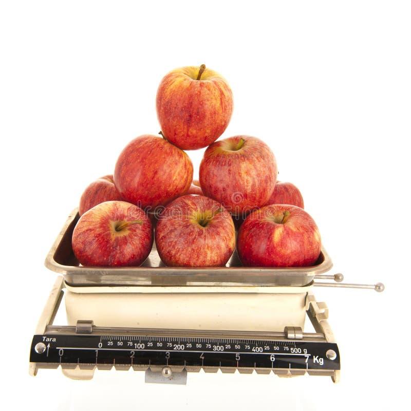 重量标度新鲜的苹果被隔绝在白色背景 免版税图库摄影