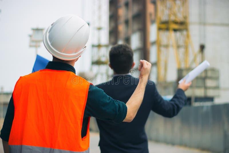 重音和建设者工头工作者的在显示在错误工作的房屋建设的顾客有盔甲的和背心拳头 免版税库存图片