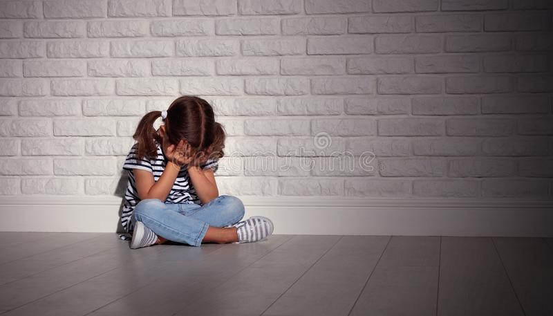 重音的生气哀伤的哀伤的儿童女孩哭泣在空的黑暗的墙壁 免版税库存图片