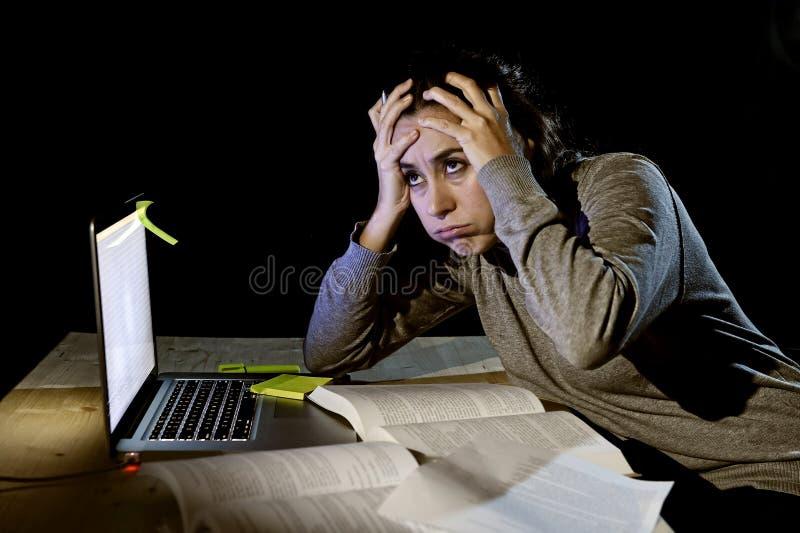 重音的年轻绝望大学生女孩检查的后学习与书和计算机膝上型计算机的在晚上 库存图片