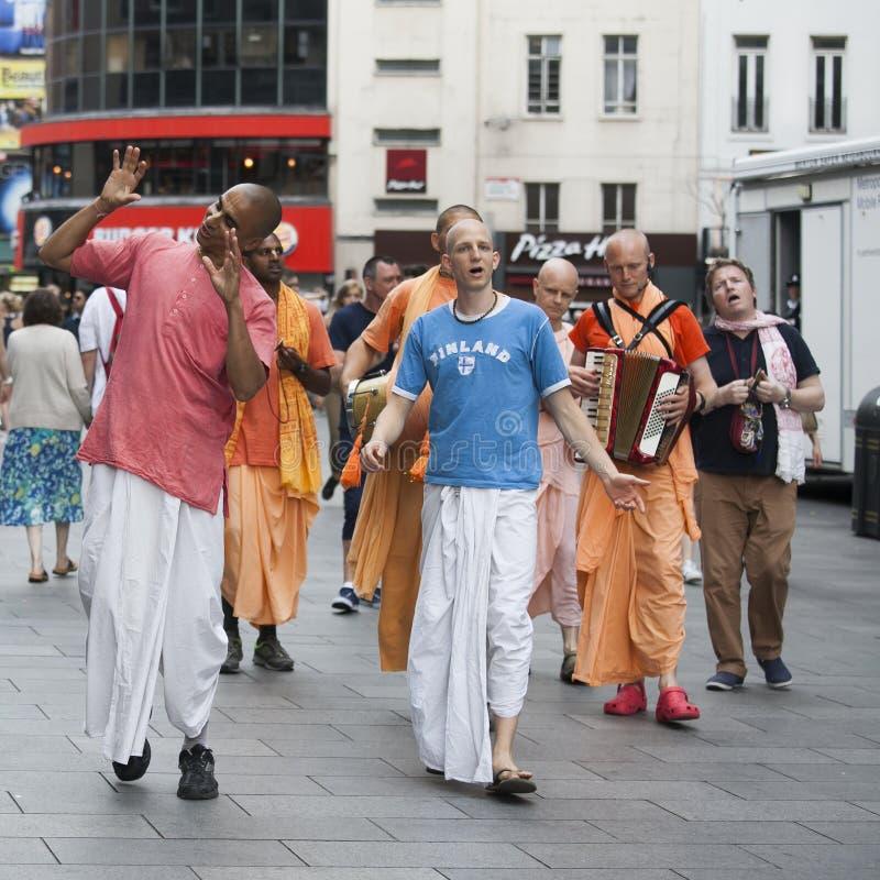 野兔克里希纳追随者步行沿着向下伦敦`在他们的橙色长袍的s牛津街 免版税库存图片