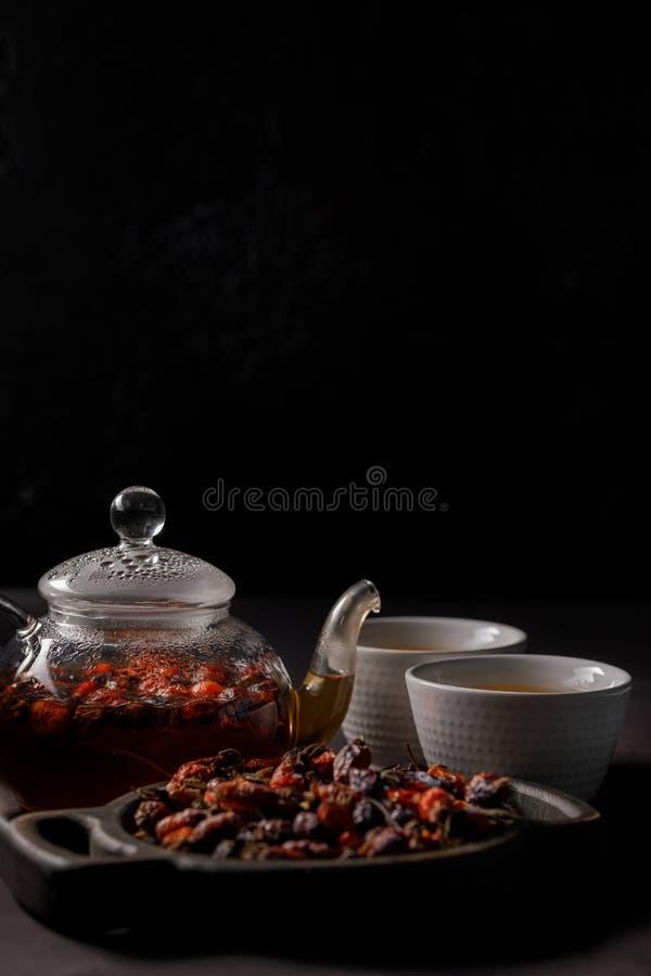 野玫瑰果茶 维生素饮料 茶壶和杯子新近地酿造的维生素野玫瑰果,一种黑暗的心情 复制空间 库存照片