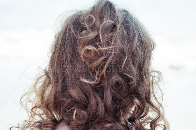 """野生卷曲金发碧眼的女人从与卷发维护和修饰的顶头â€的后面缠结了小孩景色的头发""""孩子 库存照片"""