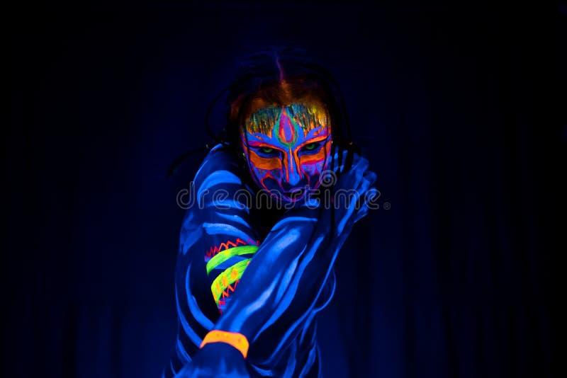 野生和狂热年轻赤裸bodyarted妇女特写镜头画象蓝色发光的紫外油漆和黄色眼睛的 图库摄影