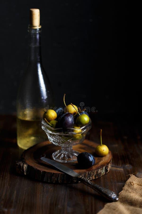 野生梨和李子在一个玻璃碗和一个瓶自创梨在木接近的背景喝酒 土气概念 免版税图库摄影