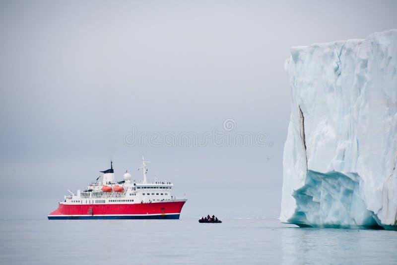 野生生物远征船在北极冰墙壁旁边停泊 库存照片