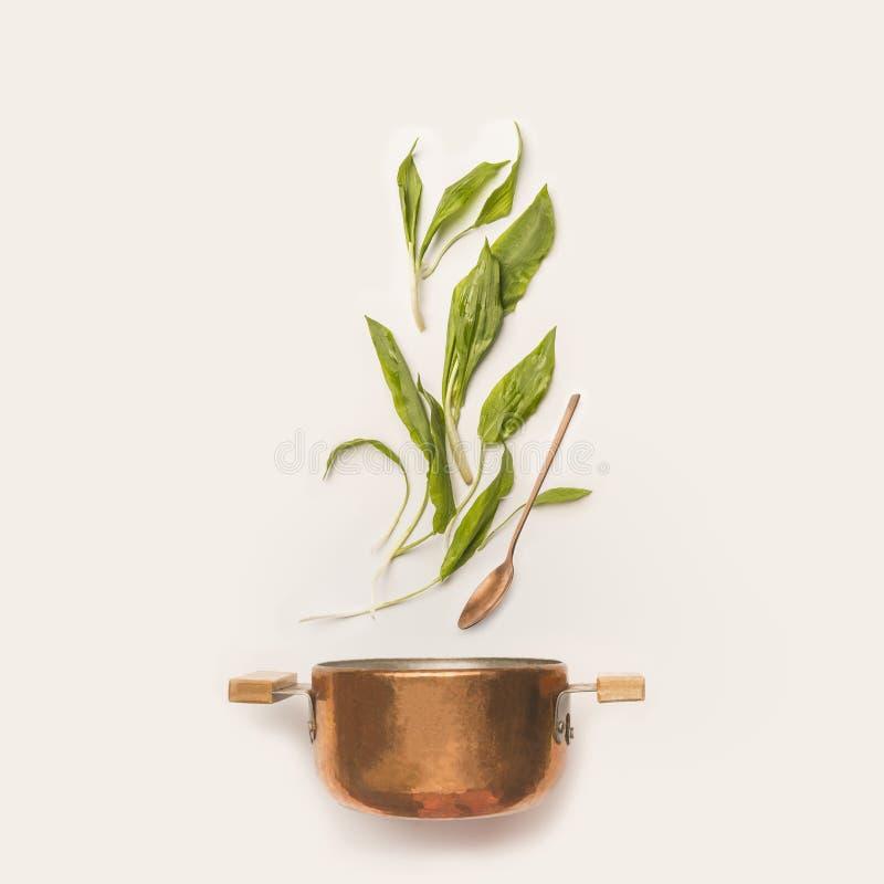 野生蒜叶子和烹调罐有匙子的在白色背景 免版税库存图片