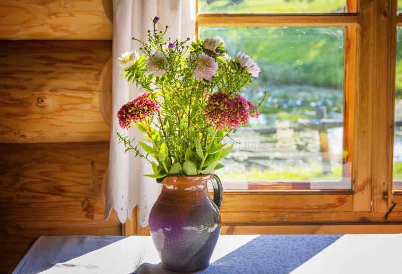 野花花束在一个水罐的在窗口 库存照片