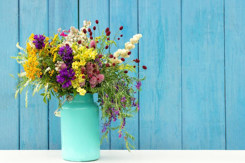 野花花束在starm的锡罐在背景蓝色木板的花瓶 明信片拷贝空间字法文本的模板或 库存图片
