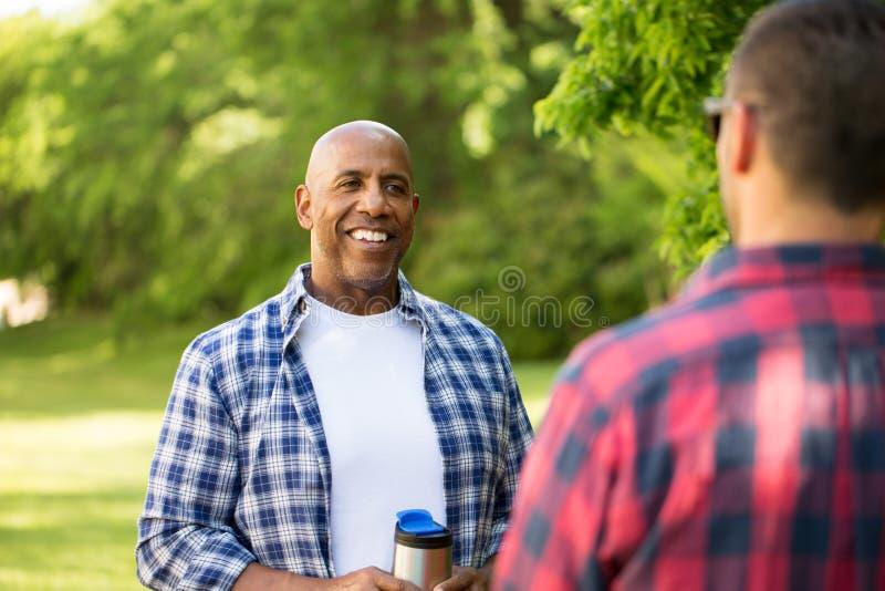 野营不同种族的小组的朋友谈话和 免版税库存照片