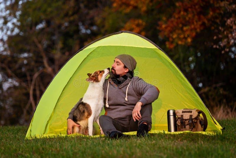 野营与宠物,友谊在人和他的狗之间 免版税库存图片