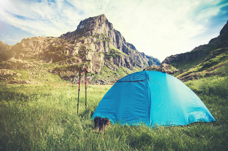 野营与迁徙的杆和起动旅行生活方式的落矶山风景和帐篷 免版税库存照片