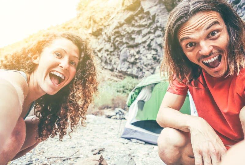 野营和做selfie的老牛愉快的爱恋的夫妇使用流动智能手机照相机-享用阵营帐篷的年轻人 库存照片
