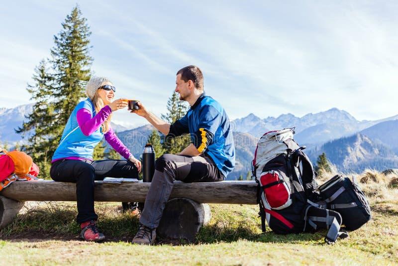 野营和喝在山的夫妇远足者 免版税库存照片