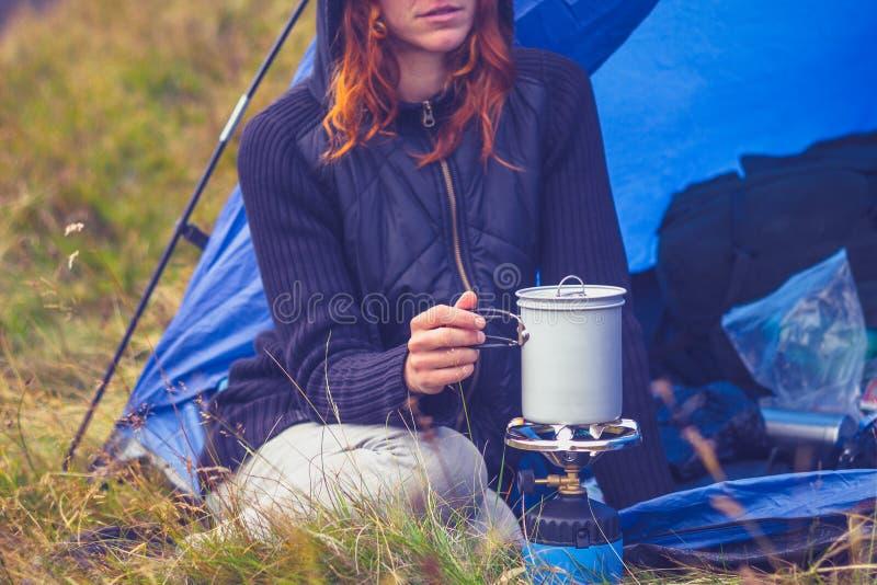 野营和烹调与便携式的火炉的妇女 免版税库存照片
