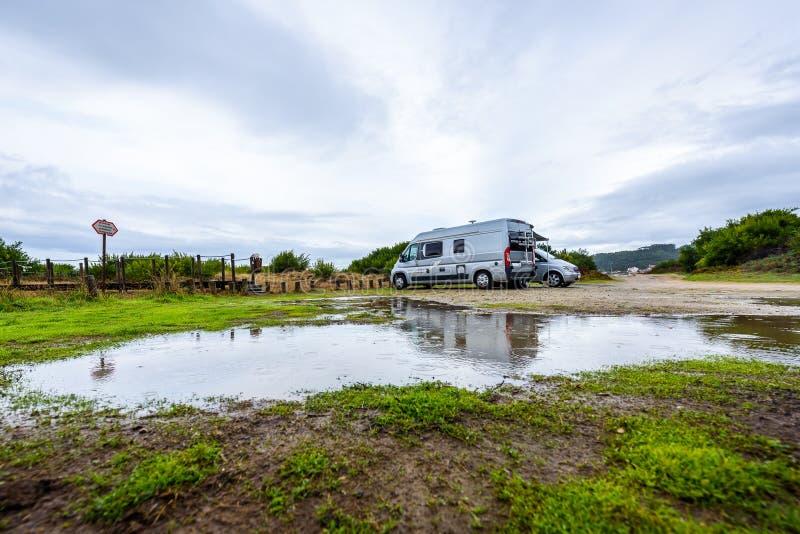 野营在与雨水坑的下雨天的Campervan或motorhome 免版税图库摄影