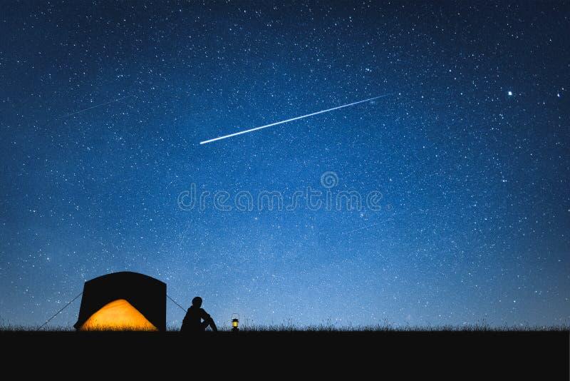 野营在山和夜空的旅客剪影与星 空间背景 免版税库存照片