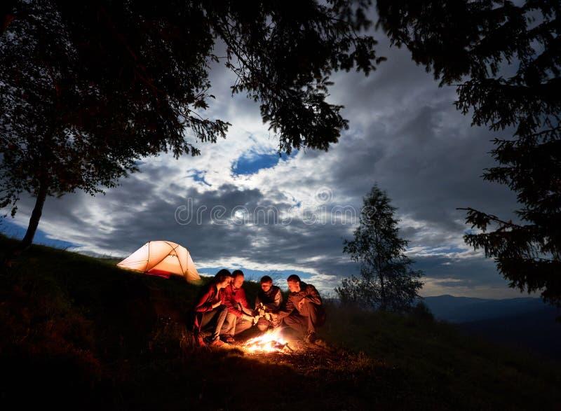 野营在山 在火附近坐用啤酒享受假日的朋友 免版税库存图片