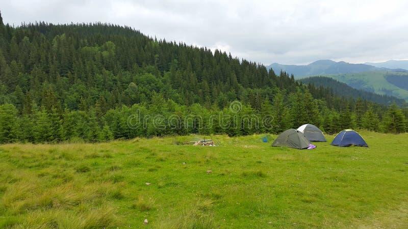 野营在山 在背景山的三个帐篷 免版税库存照片