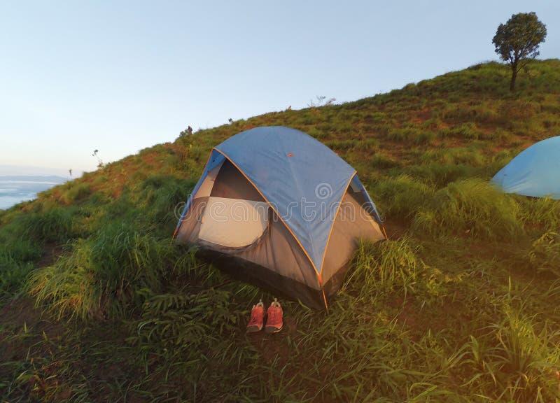 野营在山 在青山的旅游帐篷 在帐篷前面的一双桃红色鞋子 库存图片