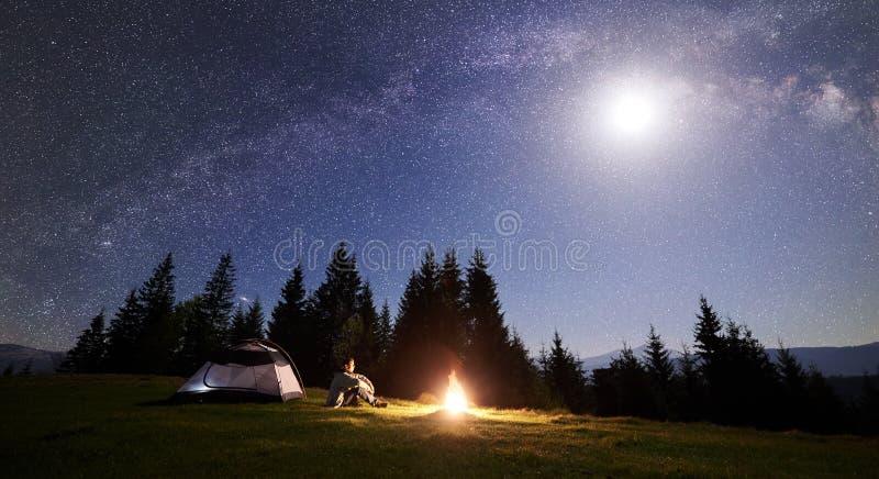 野营在旅游帐篷附近的男性远足者enjoyng夜在营火在蓝色满天星斗的天空和银河下 免版税库存照片