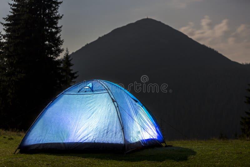 野营在晚上的夏天 在绿色清洁的有启发性旅游帐篷在遥远的山背景 免版税库存照片