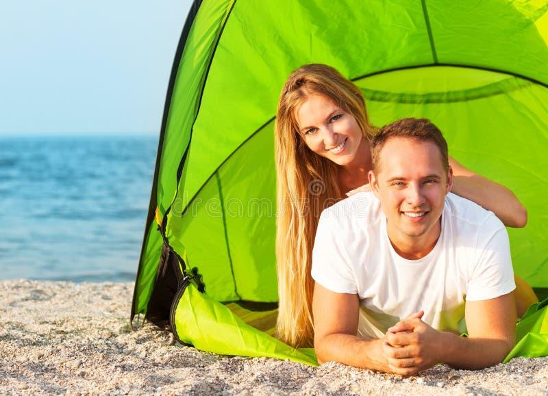 野营在海滩的愉快的年轻夫妇 库存图片
