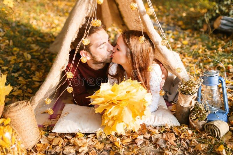 野营在秋天自然的男人和妇女远足者 野营在帐篷的愉快的年轻夫妇背包徒步旅行者 图库摄影