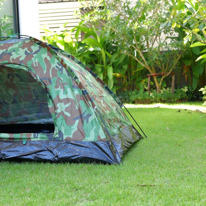野营在绿草领域营地,旅行的设备的帐篷 库存照片