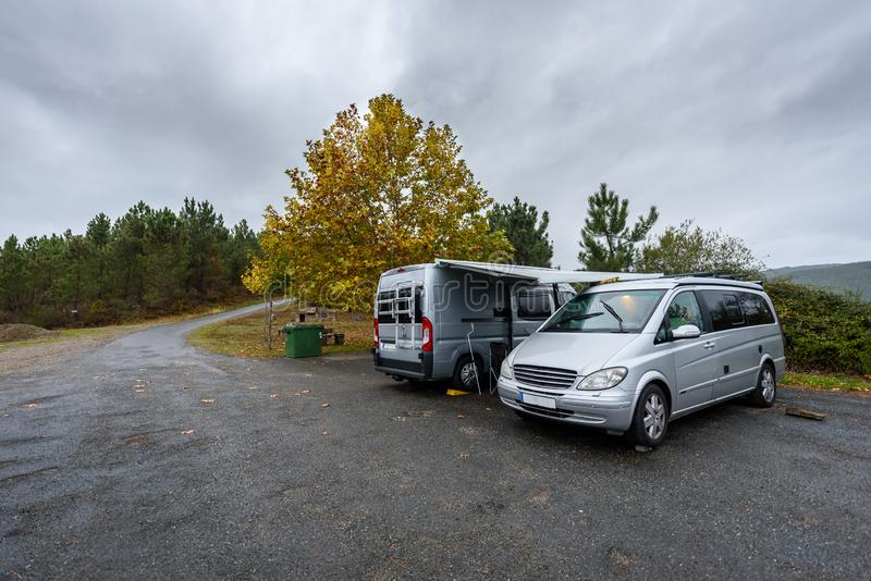 野营在自然停车处的下雨天的Campervan和motorhome 图库摄影