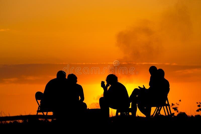 野营的坐的人们在反对日落的营火附近 免版税库存照片