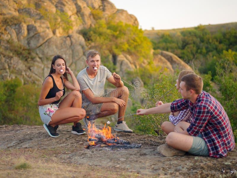 野营的学生临近在自然本底的篝火 吃蛋白软糖的逗人喜爱的夫妇 野餐天概念 复制空间 库存照片