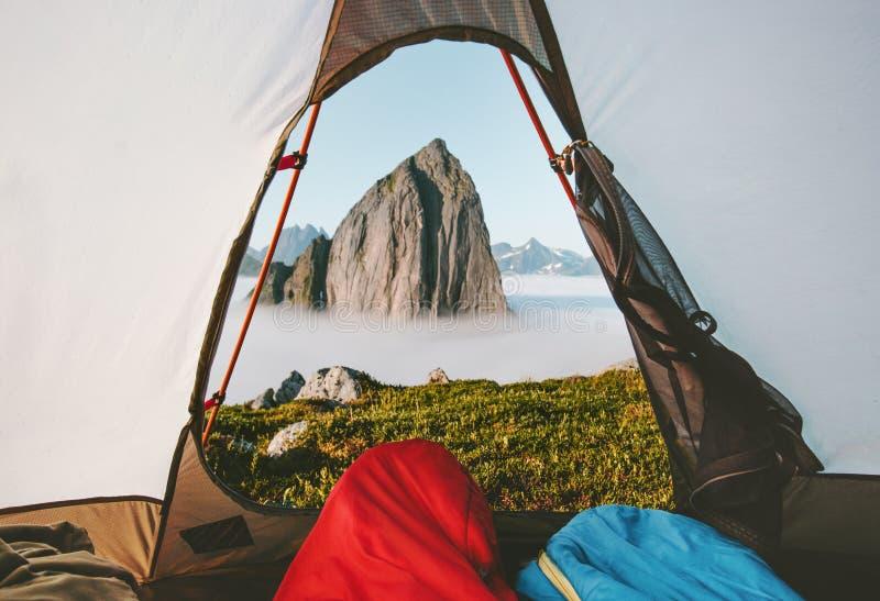 野营的帐篷山早晨视图在睡袋享用的旅行夫妇 免版税库存照片