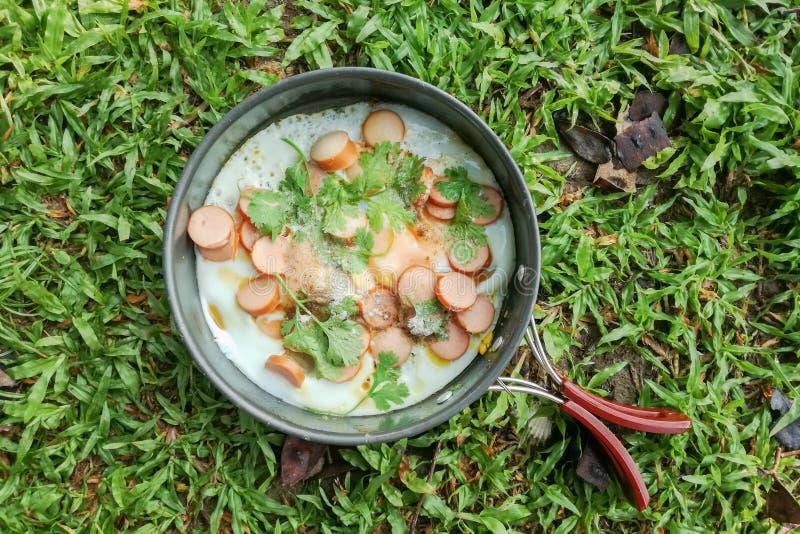 野营的早餐用在一个平底锅的煎蛋用切的香肠和在草背景的菜 顶视图 免版税图库摄影