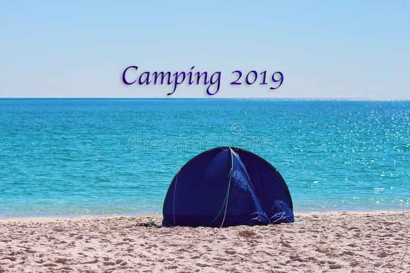 野营的2019文本-在一白色硅土沙滩的一个小蓝色树荫帐篷在Whitsund 库存图片