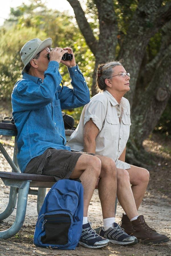 野营资深的夫妇远足,鸟的监视人和 免版税库存照片