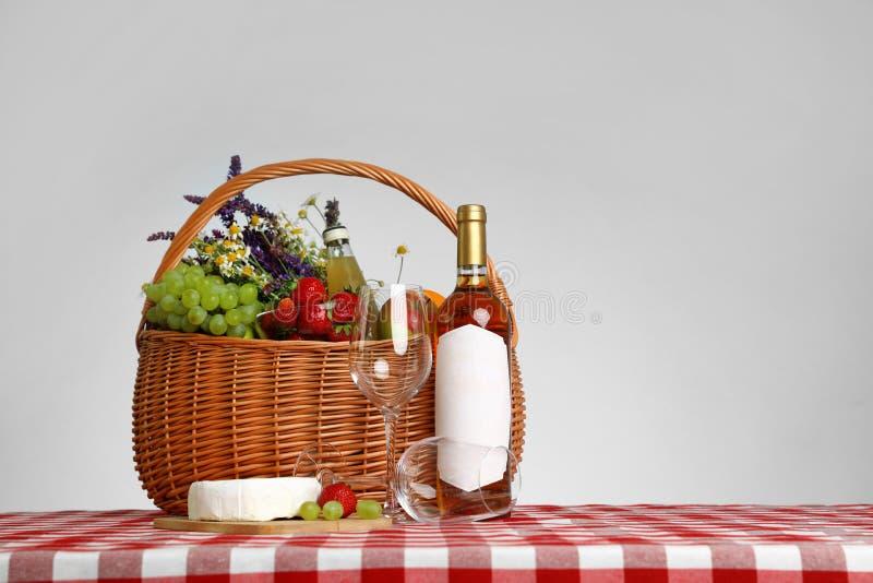 野餐在方格的桌布的篮子用酒和产品反对白色背景 库存图片