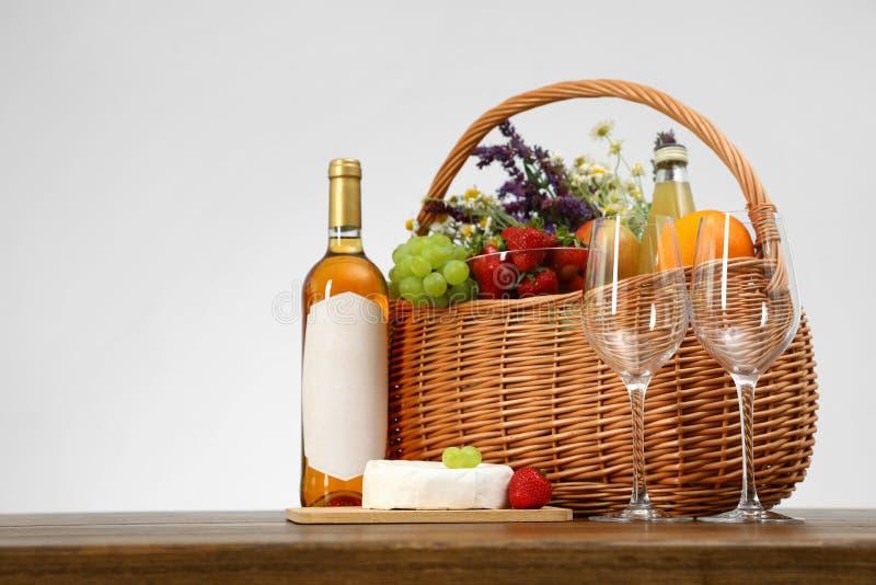 野餐在木桌上的篮子用酒和产品反对白色背景 图库摄影