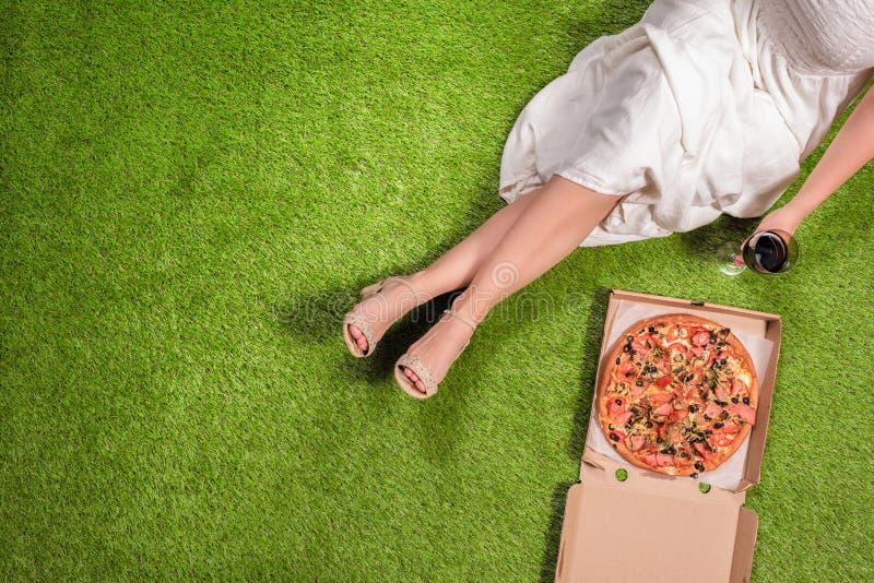 野餐在草的庭院里 在一年轻女人的鸟瞰图一件白色夏天礼服的用在箱和一杯的一比萨酒 库存照片