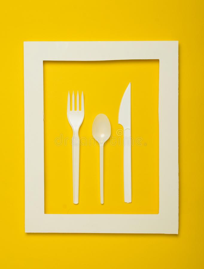 野餐的塑料利器在黄色背景的一个白色框架 一把一次性匙子,叉子,刀子 顶视图, minimalistic趋向 库存图片