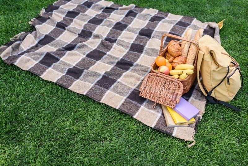 野餐篮子、背包和书大角度看法在格子花呢披肩 库存照片