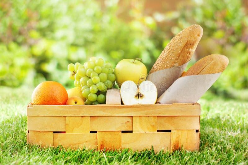 野餐篮子新鲜食品面包生物有机果子 免版税库存图片